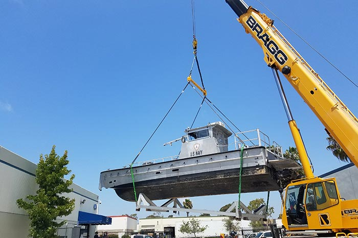 image of a navy boat being hoisted in the air with a crane